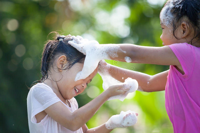 Two happy asian children girl having fun to bath. And play with foam together in outside stock image