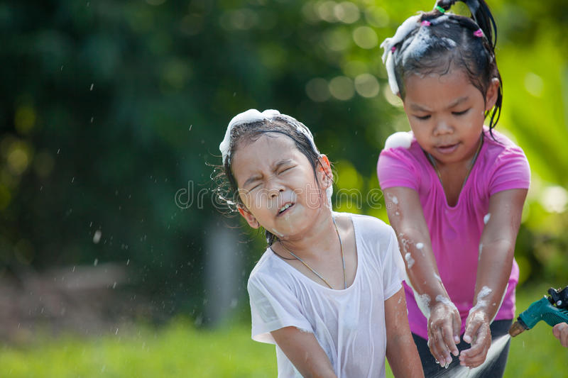 Two happy asian children girl having fun to bath. And play with water together in outside royalty free stock photos