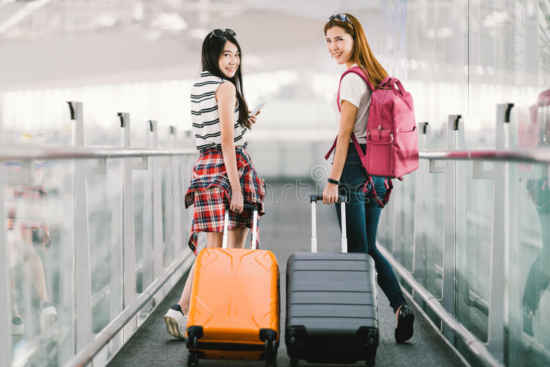 Two happy Asian girls traveling abroad together, carrying suitcase luggage in airport. Air travel or holiday vacation concept royalty free stock photos