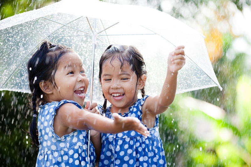 Two happy asian little girls with umbrella. Having fun to play with the rain together stock photography