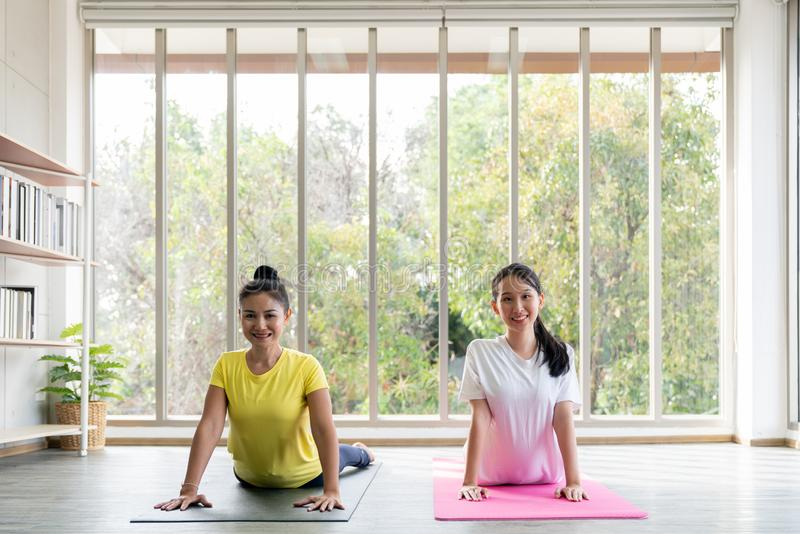 Two happy asian women in yoga poses in yoga studio with natura llight setting scene / exercise concept / yoga practice / copy. Space / yoga studio royalty free stock photos