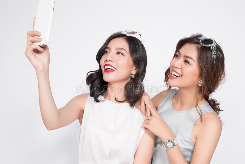 Two happy asian young women with smartphone taking selfie stock photo