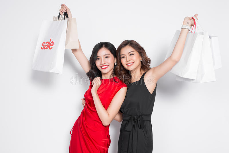 Two happy attractive young women with shopping bags on white background royalty free stock photography