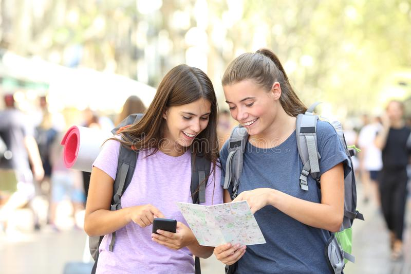 Happy backpacker friends searching location. Two happy backpacker friends searching location in a map in the street royalty free stock photos
