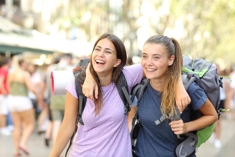 Two happy backpackers laughing enjoying vacation. Front view portrait of two happy backpackers laughing enjoying vacation in a city street royalty free stock image