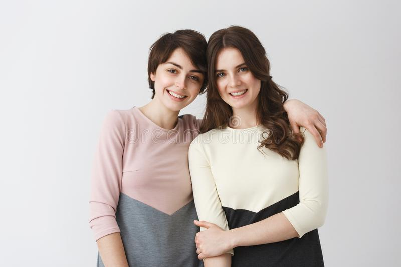 Two happy beautiful girls being friends from childhood, posing for family photo album before moving to another city for royalty free stock photos