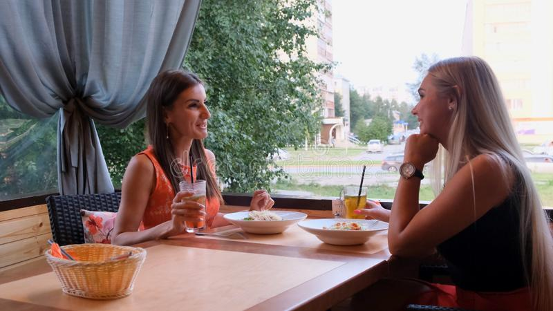 Two happy beautiful girls having fun in a cafe in sunny summer day. stock photos