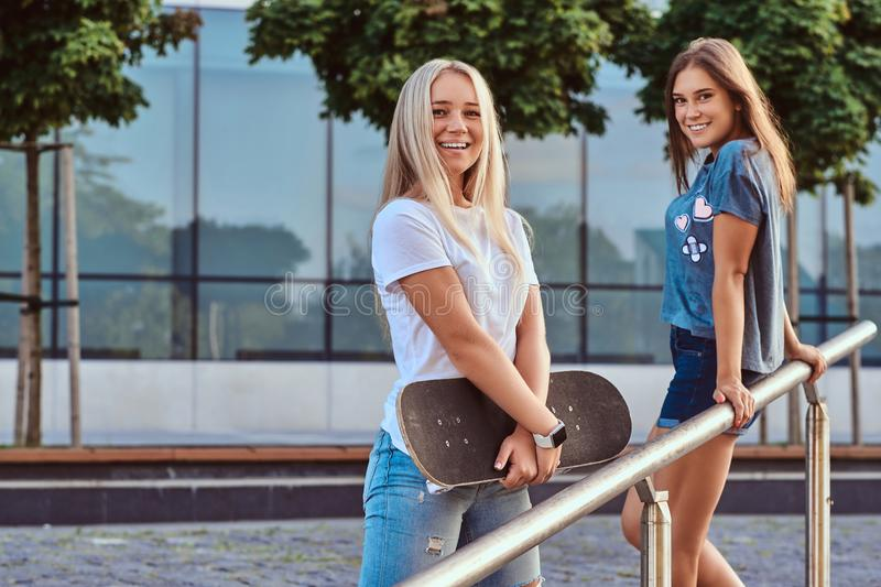Two happy beautiful hipster girls standing with skateboard on a background of the skyscraper. stock photos