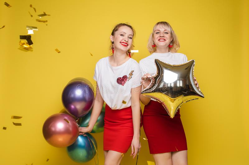 Two happy beautiful woman friend celebrating posing surrounded by colorful air balloon confetti stock images