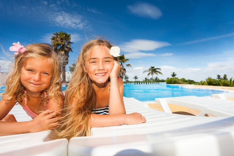 Happy girls sunbathing by outdoor swimming pool. Two happy blond age-diverse girls sunbathing by the outdoor swimming pool stock images