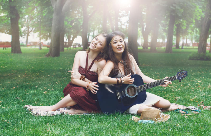 Two happy boho chic stylish girlfriends with guitar, picnic stock photo