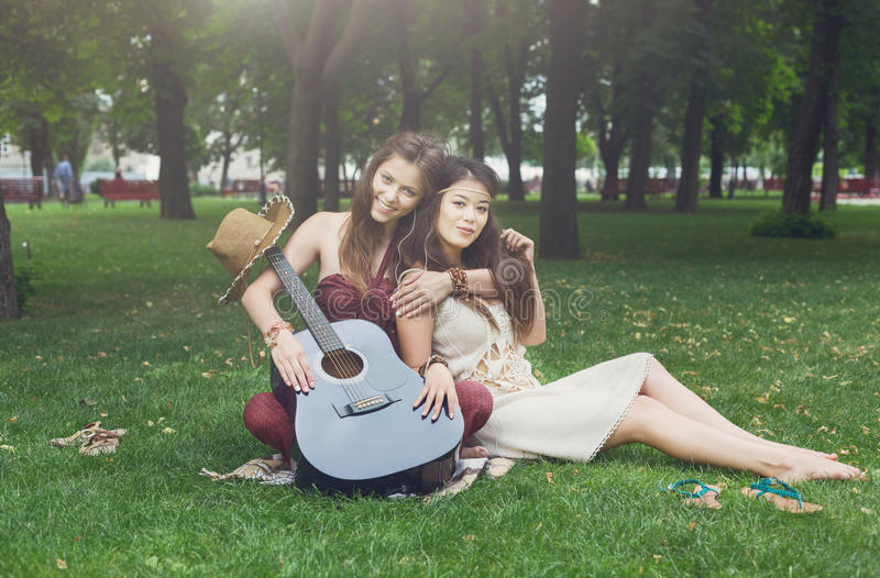 Two happy boho chic stylish girlfriends picnic in park royalty free stock photos