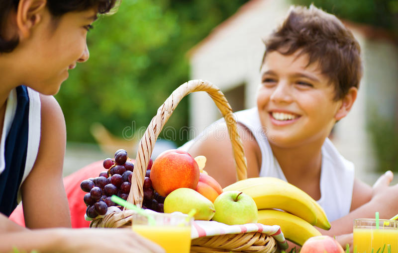 Two happy boy on picnic. Photo of two happy boy on picnic in park, brothers lying down on meadow and enjoying fresh sweet fruits, teens have lunch outdoors royalty free stock photo