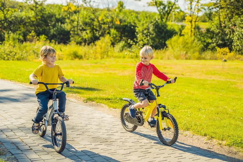 Two happy boys cycling in the park stock images
