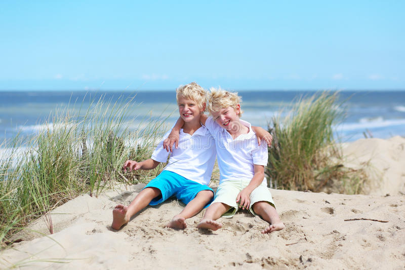 Two happy boys playing in dunes at the beach stock photo