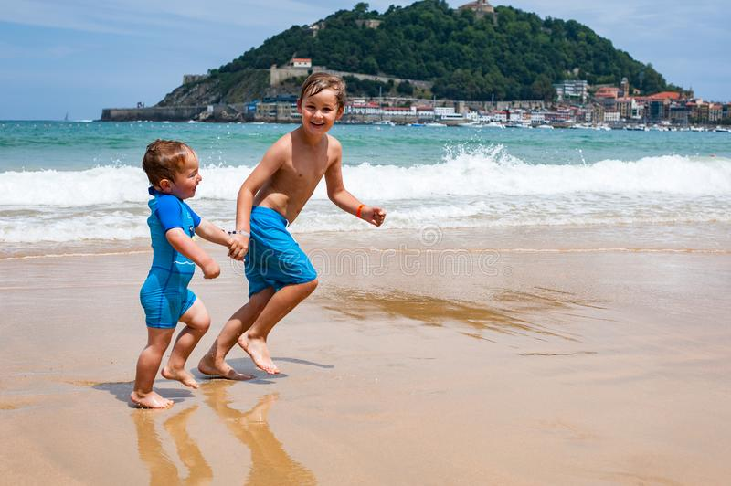 Two happy boys in running along a beach making big splashes royalty free stock photos