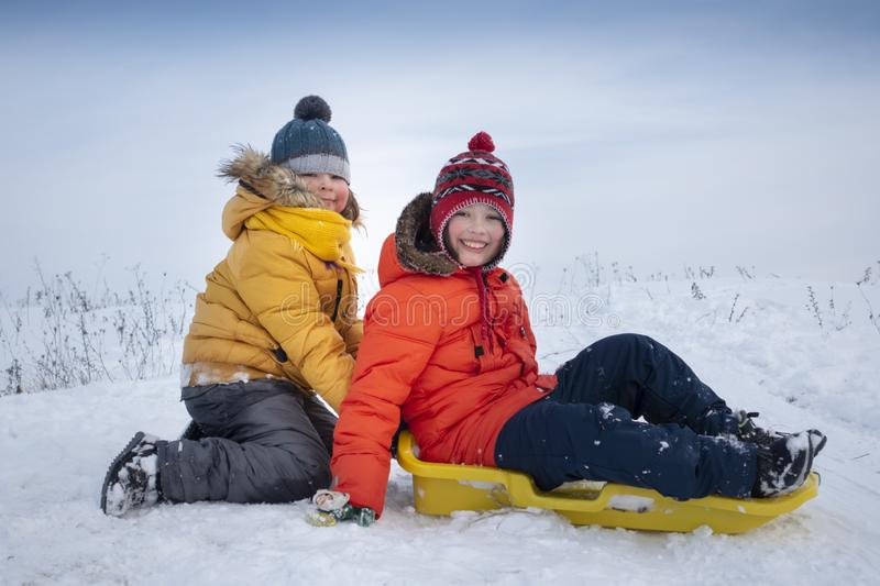 Two happy boys on sled and Skis in winter outdoors royalty free stock photos