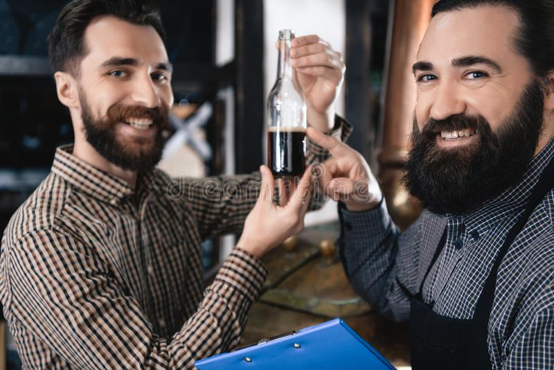 Two happy brewers welded bottle of dark beer. Production of dark kraft beer. Process of beer manufacturing. Brewing. Brewery royalty free stock photography