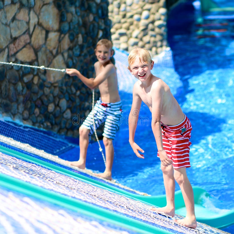 Two happy brothers having fun in aqua park stock photo