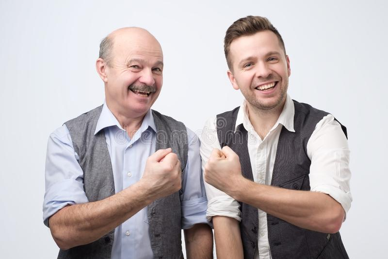 Two happy buddies wearing shirt and vest smiling and showing fis stock photo