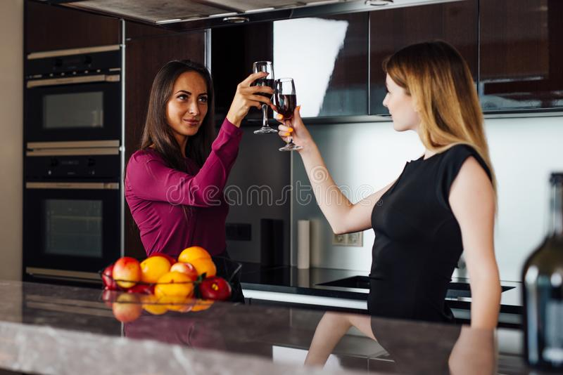 Two happy business partners raising glasses of wine proposing a toast for a successful mutual cooperation.  royalty free stock image