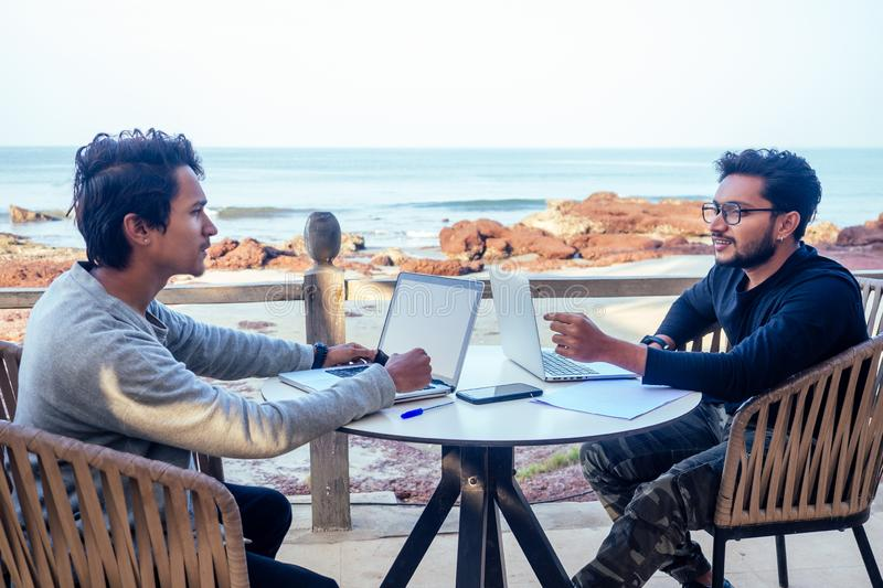 Two happy businessmen discussing freelancer strategy in a meeting, Indian business man remote work freelancing sitting royalty free stock image