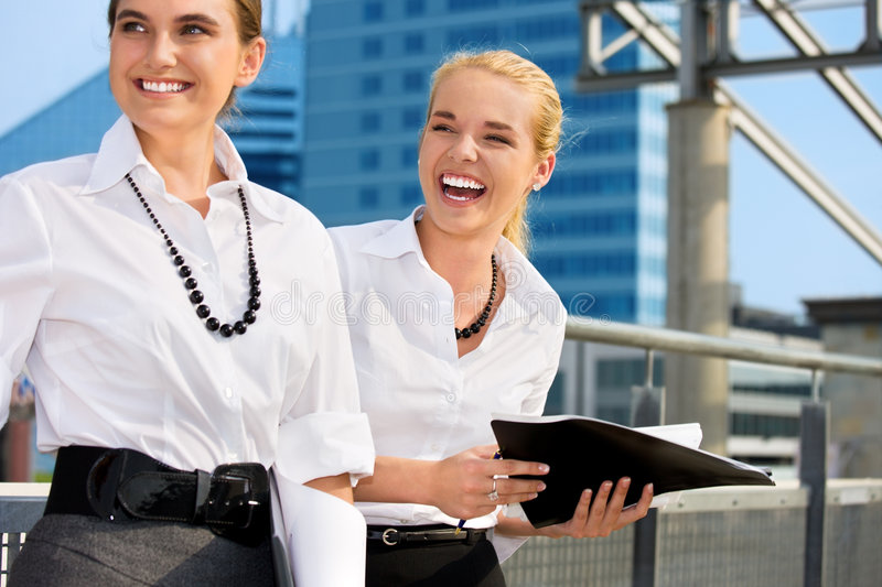 Two happy businesswomen with folders. (focus on blonde stock photo
