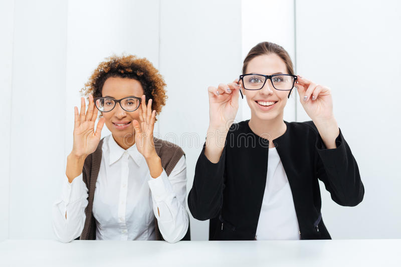 Two happy businesswomen having fun with glasses in office stock images