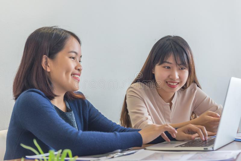 Two smiling businesswomen using laptop while having business meeting royalty free stock photography