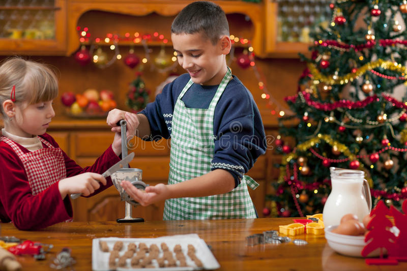 Two happy child preparing cookie for family dinner on Xmas eve. Kitchen decorated for Christmas. Family, holiday, kids lifestyle conceplt royalty free stock photos