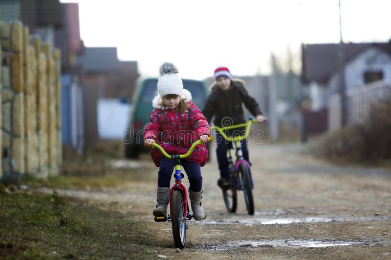 Two happy children boy and girl riding bicycles outdoors in cold royalty free stock image