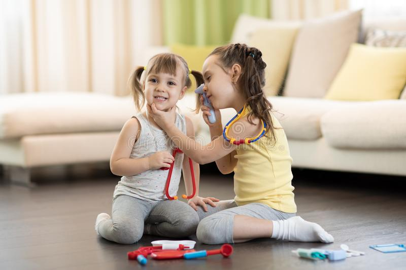 Two happy children, cute toddler girl and older sister, playing doctor and hospital using stethoscope toy and other medical toys, stock photos