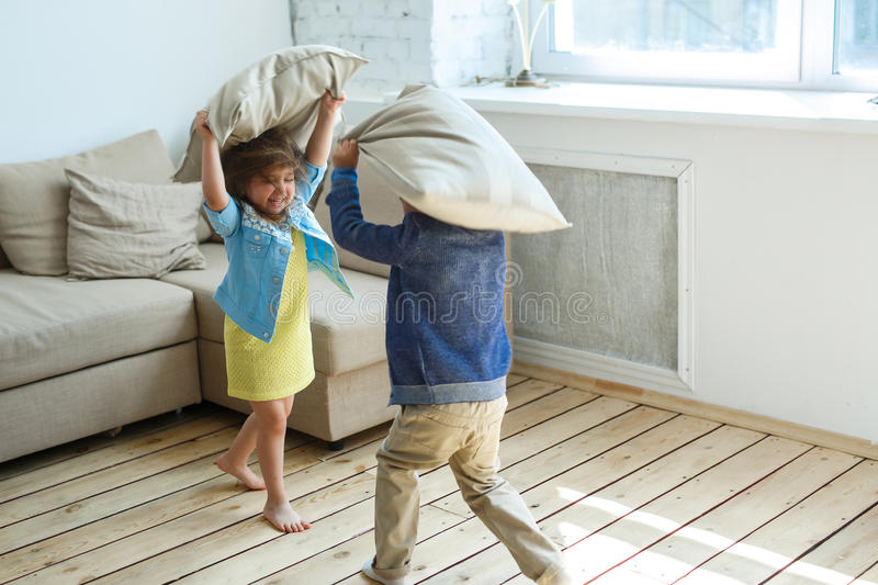 Two happy children is fighting a pillows each other royalty free stock photography
