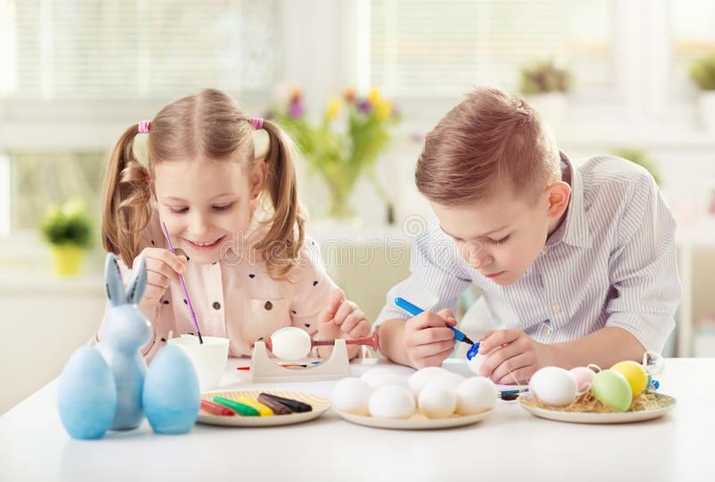 Two happy children having fun during painting eggs for easter in royalty free stock image