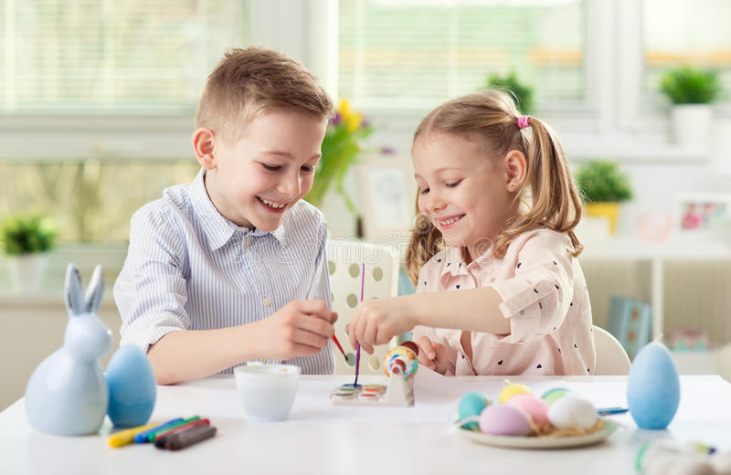 Two happy children having fun during painting eggs for easter in stock photography