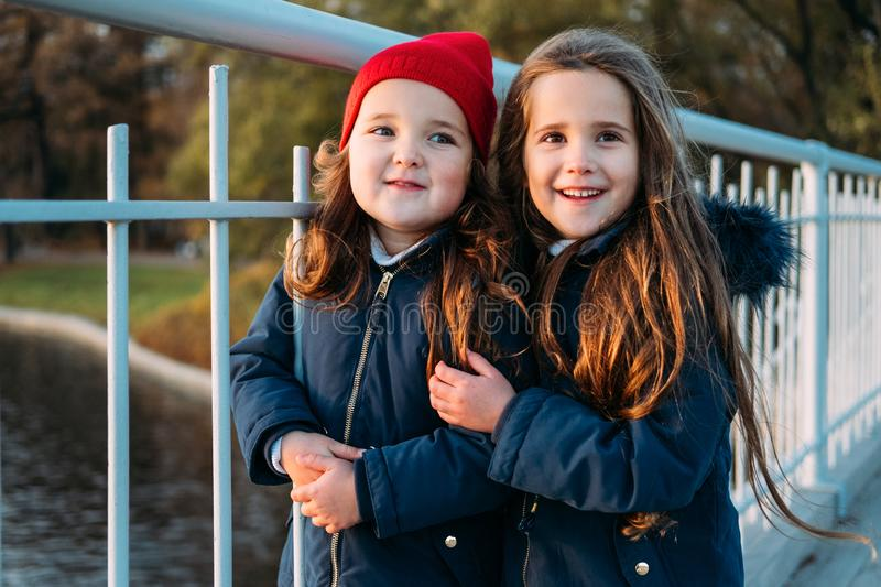 Two happy children hugging in autumn park. Close up sunny lifestyle fashion portrait of two beautiful caucasian girls outdoors,wea stock photo