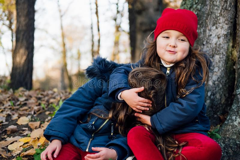 Two happy children hugging in autumn park. Close up sunny lifestyle fashion portrait of two beautiful caucasian girls outdoors,wea stock image