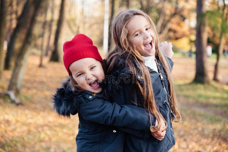 Two happy children hugging in autumn park, smiling, looking at camera. Cute stylish children wearing trendy outfit in navy and red royalty free stock images