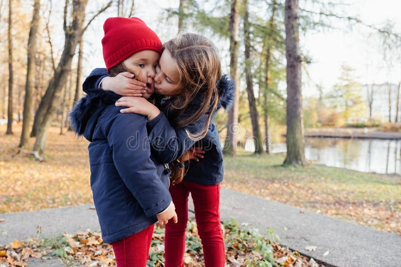 Two happy children hugging and kissing in autumn park. Close up sunny lifestyle fashion portrait of two beautiful caucasian girls stock photo