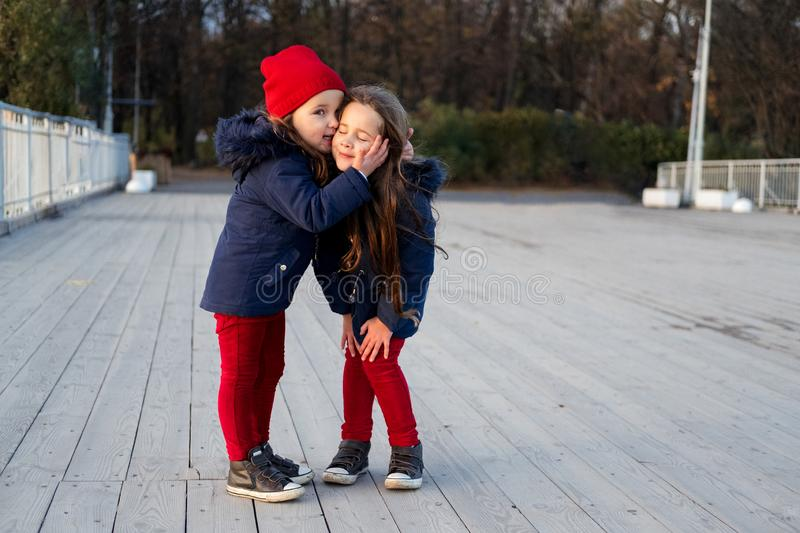 Two happy children hugging and kissing in autumn park. Close up sunny lifestyle fashion portrait of two beautiful caucasian girls royalty free stock photography