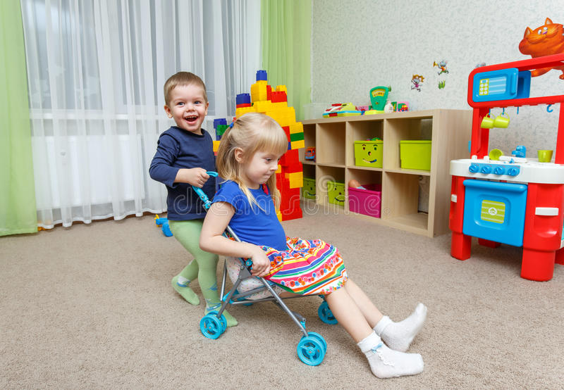 Two happy children play with toy stroller in daycare stock photography