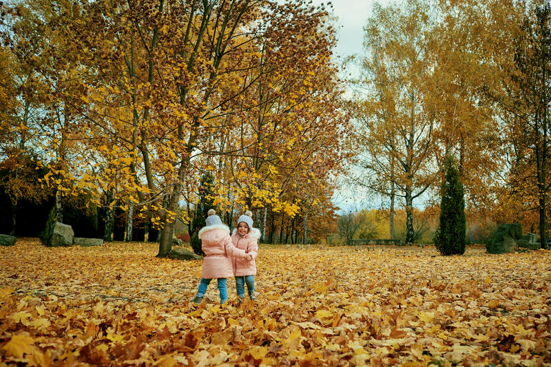 Two happy children playing in autumn clothes in the park. royalty free stock photos