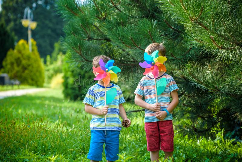 Two happy children playing in garden with windmill pinwheel. Adorable sibling brothers are best friends. Cute kid boy smile spring stock photography