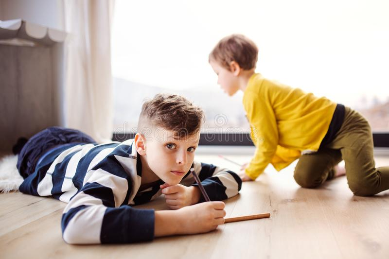 Two happy children playing at home, drawing. royalty free stock image