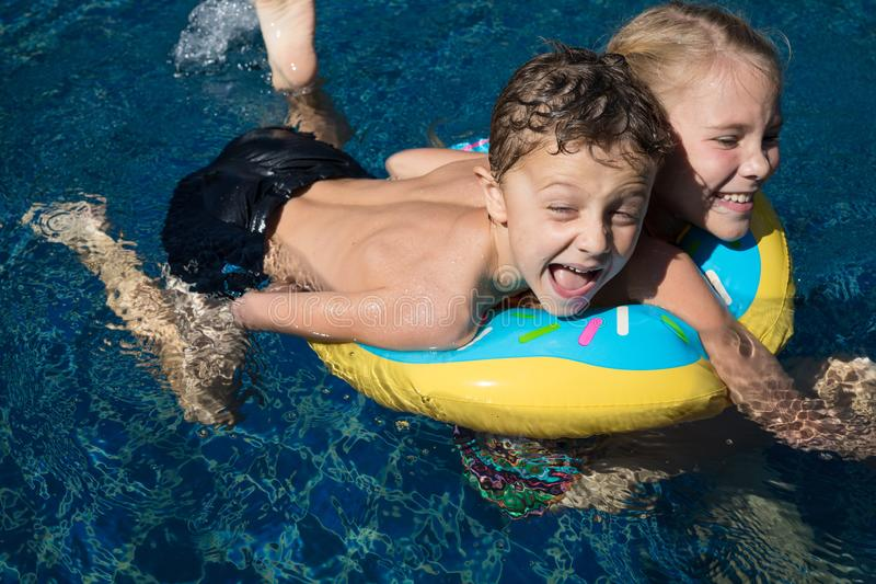 Two happy children  playing on the swimming pool at the day time stock photos