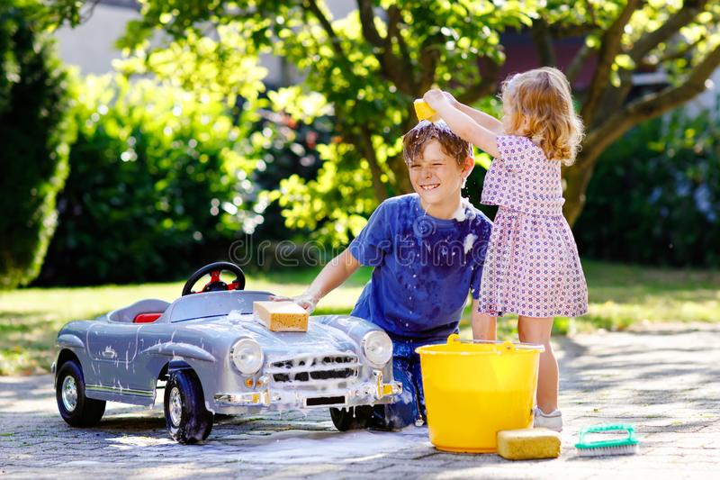 Two happy children washing big old toy car in summer garden, outdoors. Brother boy and little sister toddler girl royalty free stock photography