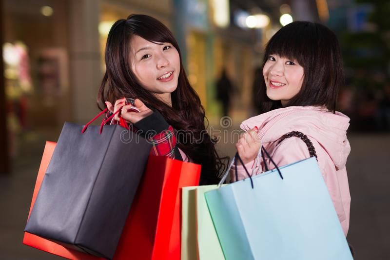Two happy chinese women with shopping bags stock photography