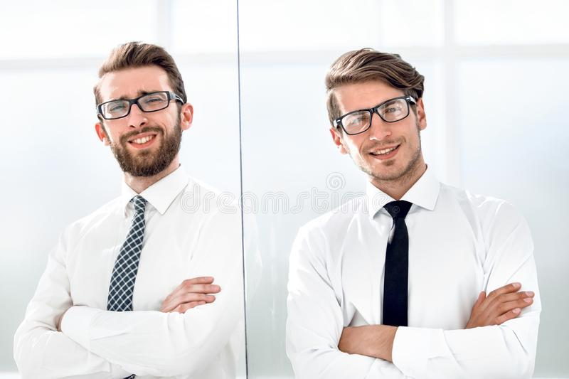 Two happy confident young businessmen standing with arms crossed in office. Business concept royalty free stock photos