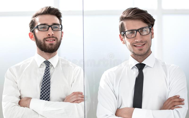 Two happy confident young businessmen standing with arms crossed in office stock photography