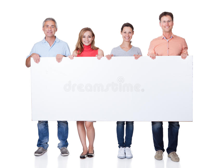 Two happy couples holding up a blank banner stock images